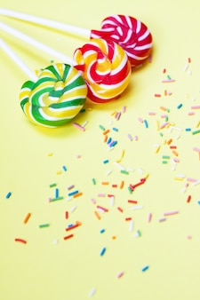 Kolorowe lizaki i konfetti na żółtym tle. słodycze na imprezę. cukier