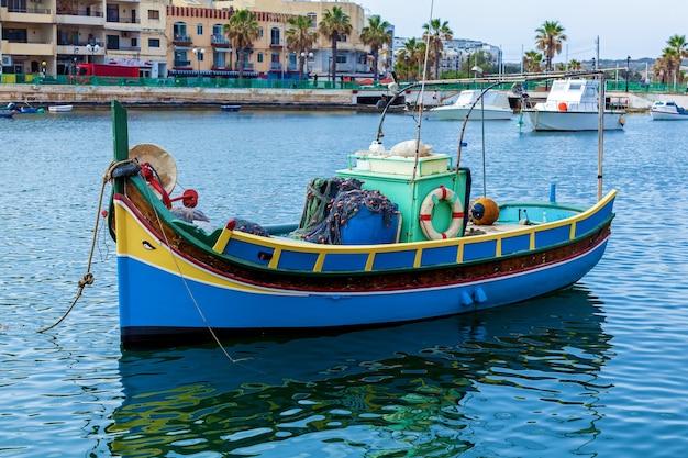 Kolorowe luzzu w pobliżu brzegu wioski rybackiej w słoneczny dzień, malta. w porcie znajduje się kuter rybacki w kolorach niebieskim i żółtym.