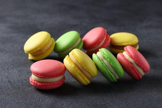Kolorowe makaroniki francuskie na ciemnoszarym tle. zbliżenie. format poziomy