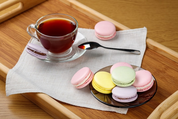 Kolorowe makaroniki i filiżanka herbaty na drewnianej tacy poranna herbata i słodycze