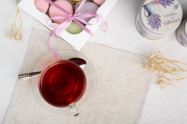 Kolorowe makaroniki i filiżanka herbaty na jasnym drewnianym stole poranna herbata i słodycze widok z góry