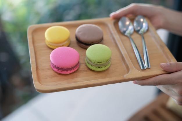 Kolorowe makaroniki i łyżka kawy na drewnianej tacy.