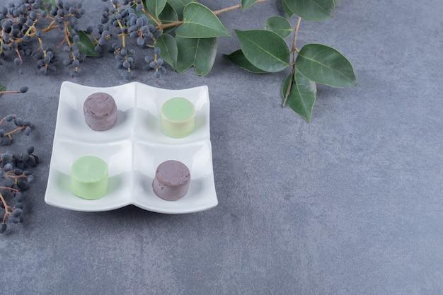 Kolorowe makaroniki na białym talerzu na szarym tle.