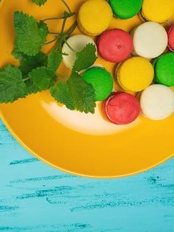 Kolorowe makaroniki na żółtym talerzu na drewnianym stole. skopiuj miejsce.