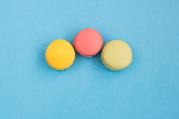 Kolorowe makaroniki, różowe, żółte i zielone makaroniki na niebieskim tle. jasna i kolorowa koncepcja. copyplace, miejsce na tekst.