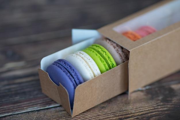 Kolorowe makaroniki w papierowym pudełku na drewnianym stole