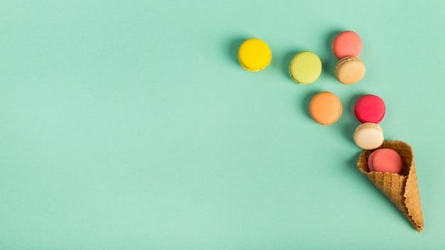 Kolorowe makaroniki wycieki z rożka waflowego na tle zielonej mięty