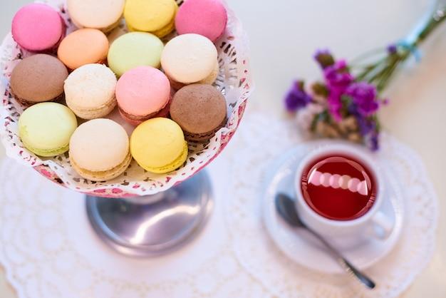 Kolorowe makaroniki z czerwoną herbatą na stole z kwiatami.