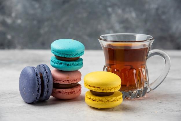 Kolorowe makaroniki z filiżanką czarnej herbaty na białym stole.