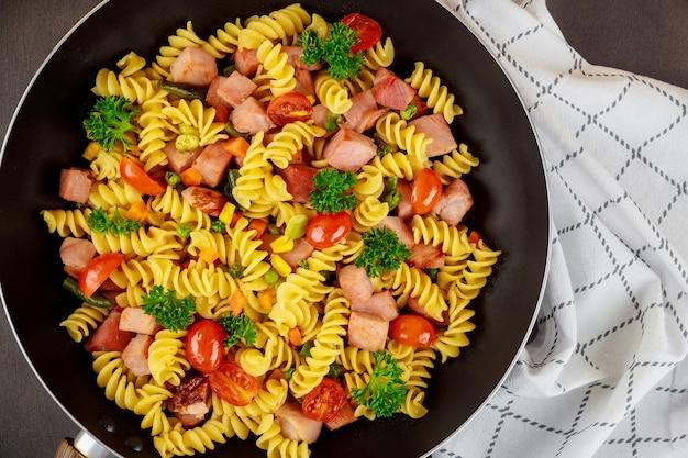 Kolorowe makarony rotini, pomidory cherry i szynka na patelni. ścieśniać. widok z góry.