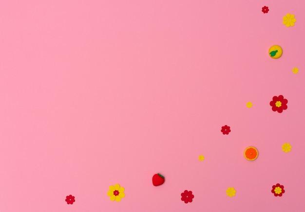 Kolorowe małe gumki z kształtami owoców i kwiatów na różowym tle z miejscem na kopię