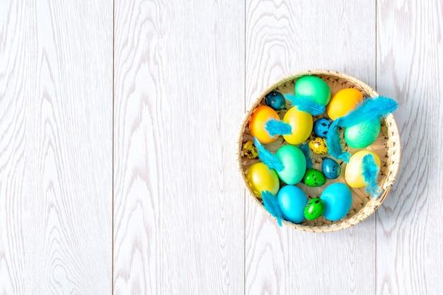 Kolorowe malowane kurczaka i przepiórcze pisanki w koszyku z piórami, wiosna, koncepcja wielkanocy, transparent.