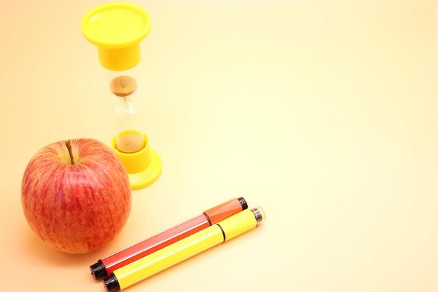 Kolorowe markery, jabłko i klepsydra. powrót do szkoły.