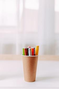 Kolorowe markery w słoiku z papieru rzemieślniczego na białym stole. przybory szkolne.