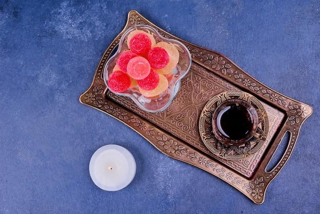 Kolorowe marmolady i szklanka herbaty earl grey w metalicznym talerzu.