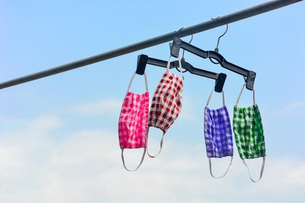 Kolorowe maski ochronne tkaniny w kratkę wiszące na wieszaku czarny kolor na zewnątrz metalowy stojak z błękitne niebo