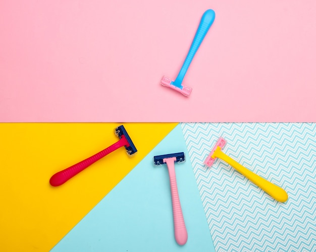 Kolorowe maszynki do golenia lub depilatory na pastelowym tle. widok z góry.