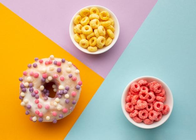 Kolorowe miski na płatki zbożowe i smaczne pączki