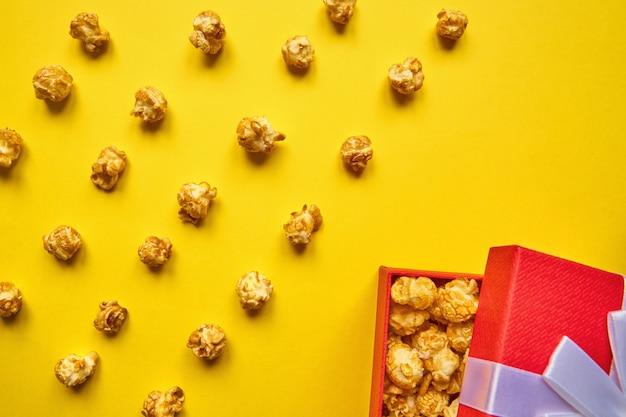 Kolorowe modne tło z karmelowym popcornem i czerwonym pudełkiem na żółtym tle