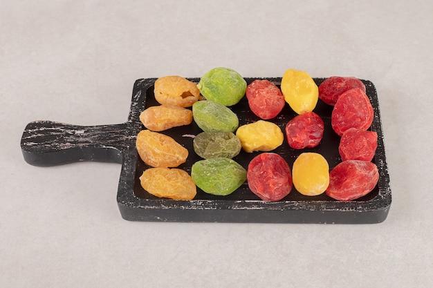 Kolorowe morele i wiśnie na czarnym drewnianym talerzu.