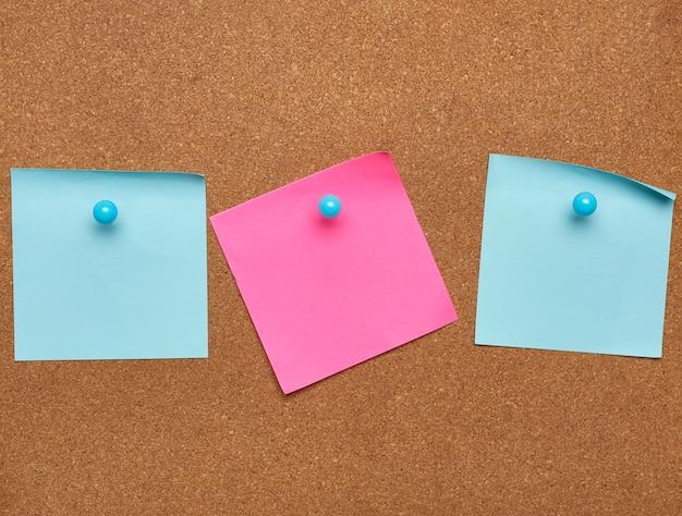 Kolorowe naklejki papierowe naklejane na brązową tablicę