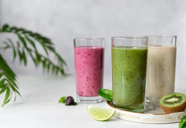 Kolorowe napoje koktajlowe ze składnikami (kiwi, banan, jeżyna) naturalne organiczne jedzenie w stylu szarym tle z zielonymi liśćmi w poziomie,