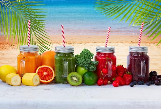 Kolorowe napoje smoothy w szklanych słoikach ze składnikami przy plaży