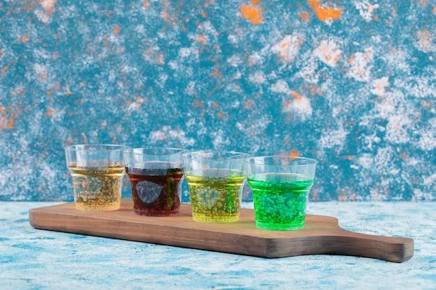 Kolorowe napoje w kubkach na drewnianym talerzu