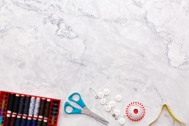 Kolorowe narzędzia do szycia i krawiectwa oraz przedmioty na jasnym tle