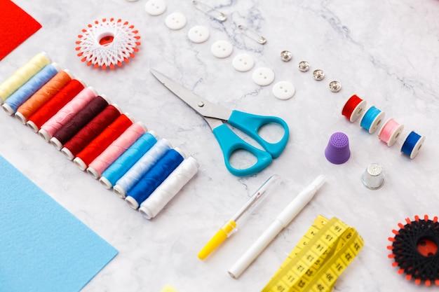 Kolorowe narzędzia i przedmioty do szycia i krawiectwa na lekkiej powierzchni