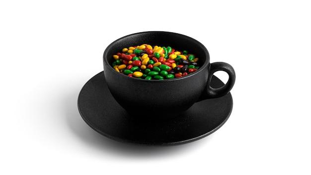 Kolorowe nasiona słonecznika czekolady w czarny kubek na białym tle.