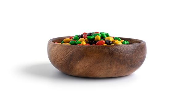 Kolorowe nasiona słonecznika czekolady w drewnianej misce na białym tle.