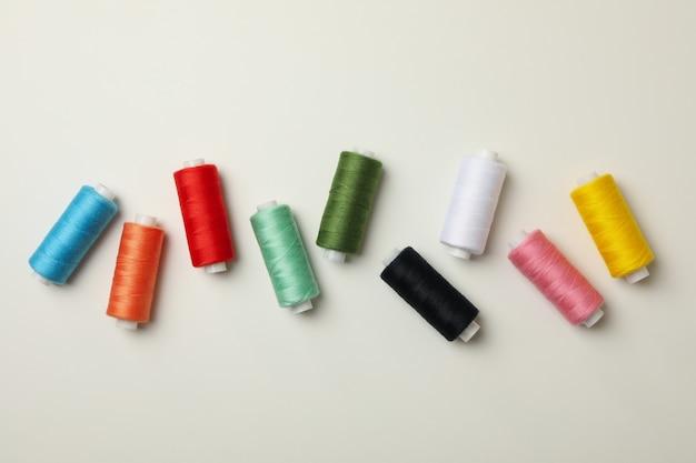 Kolorowe nici do szycia na białym tle