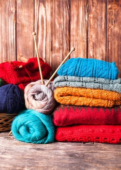 Kolorowe nici, druty i ubrania na drewnianym stole