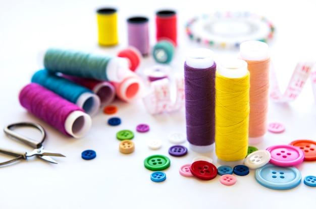 Kolorowe nici i dodatki do szycia na białej powierzchni