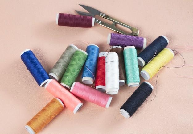 Kolorowe nici i igła w tle