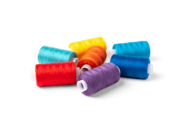 Kolorowe nici na białym tle.