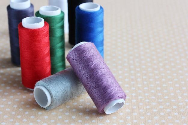 Kolorowe nici w cewkach na zbliżeniu stołu.