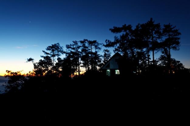 Kolorowe niebo i dom w lesie o zmierzchu