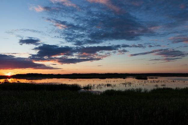Kolorowe niebo i jego odbicie w wodzie jeziora podczas zachodu słońca, krajobraz o zmierzchu
