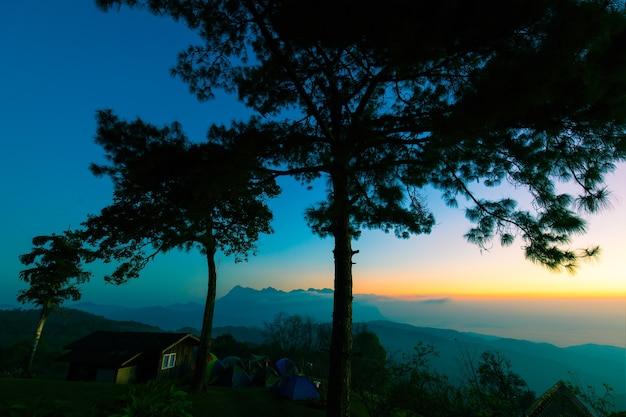 Kolorowe niebo rano nad górami w północnej tajlandii z namiotami i domem na szczycie góry.