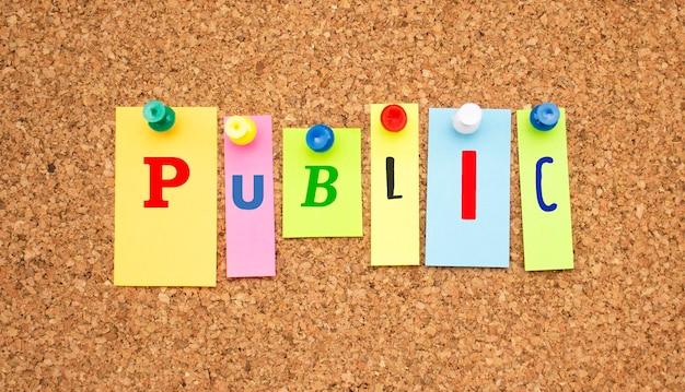 Kolorowe notatki z literami przypiętymi na tablicy słowa publicznego