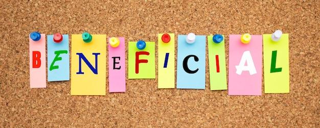 Kolorowe notatki z literami przypiętymi na tablicy. słowo beneficial. miejsce do pracy.