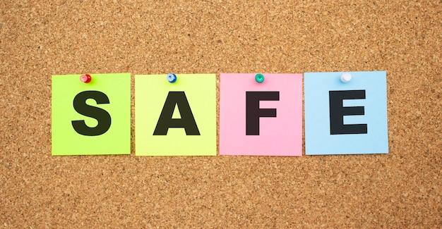 Kolorowe notatki z literami przypiętymi na tablicy. słowo bezpieczne. miejsce do pracy.