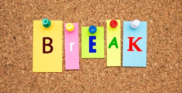 Kolorowe notatki z literami przypiętymi na tablicy. słowo break.