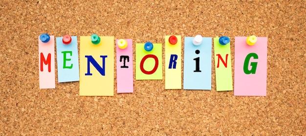 Kolorowe notatki z literami przypiętymi na tablicy. słowo mentoring