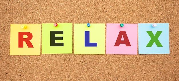 Kolorowe notatki z literami przypiętymi na tablicy. słowo relaks. miejsce do pracy.