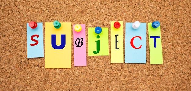 Kolorowe notatki z literami przypiętymi na tablicy. słowo temat
