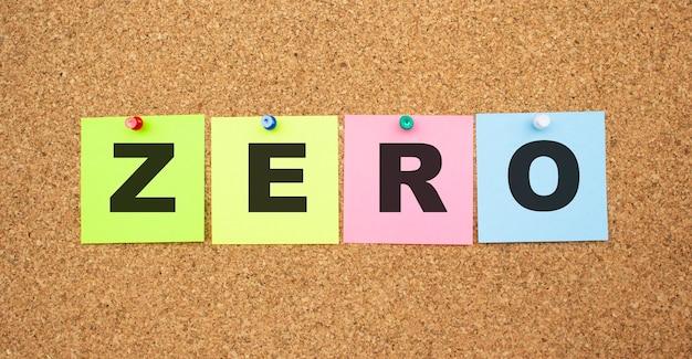 Kolorowe notatki z literami przypiętymi na tablicy. słowo zero. miejsce do pracy.