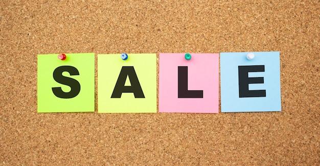 Kolorowe notatki z literami przypiętymi na tablicy. sprzedaż słowa